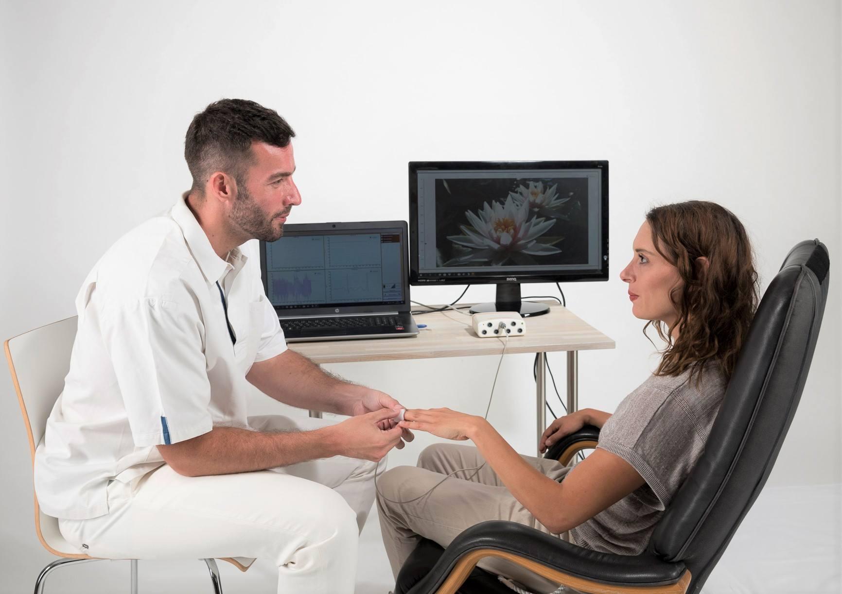 Biofeedback Geräte -Therapeut bringt Klientin den Fingersensor an.